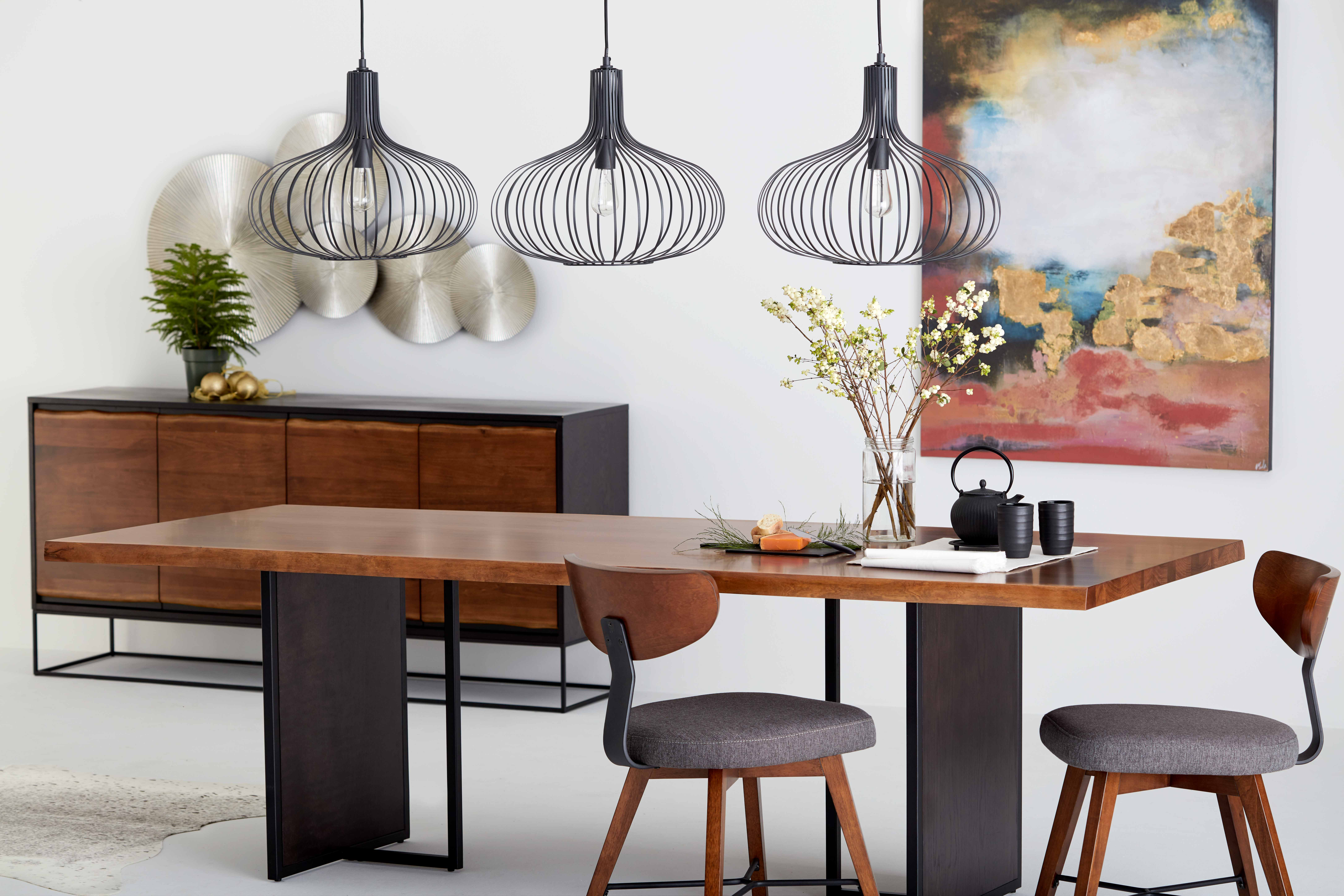 Dining room composed of a beautiful wooden and steel table surrounded by 2 chairs. Above the table there are 3 pendant lamps.