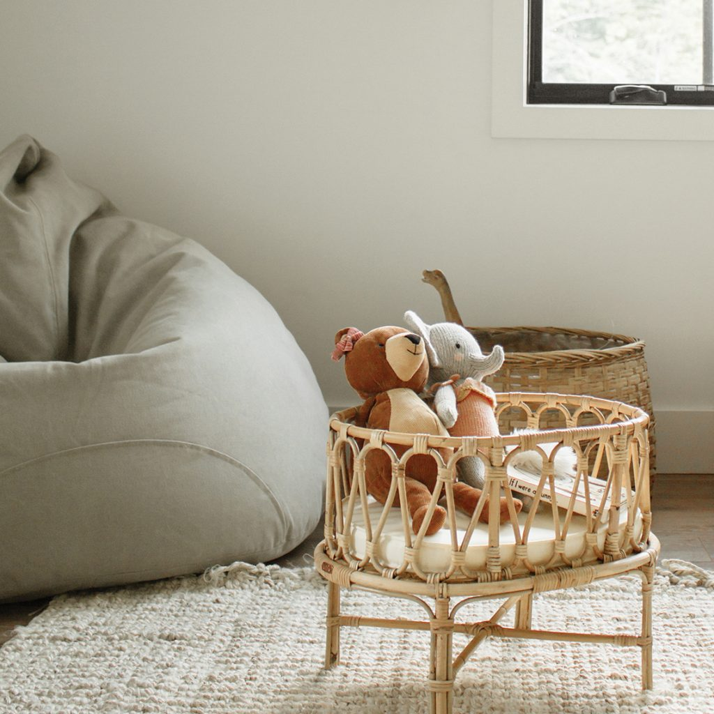 Close-up view of the bean bag and a wicker cradle with cuddly toys for children.