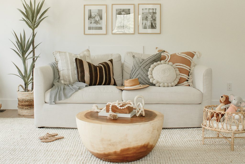 A comfortable corner composed of a beige sofa filled with cushions, a plant, framed photos on the wall, a coffee table and a soft carpet on the floor.