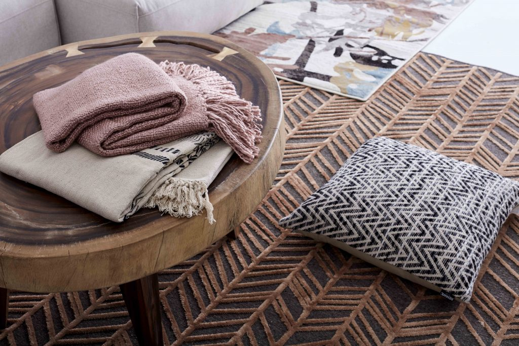 Accumulation of rugs, throws and cushions in soft and warm colours
