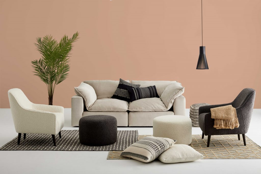 "Fabrics: a beige fabric sofa on which are placed two patterned cushions, armchairs in ""sheep's wool"" and multiplication of rugs and cushions on the floor."