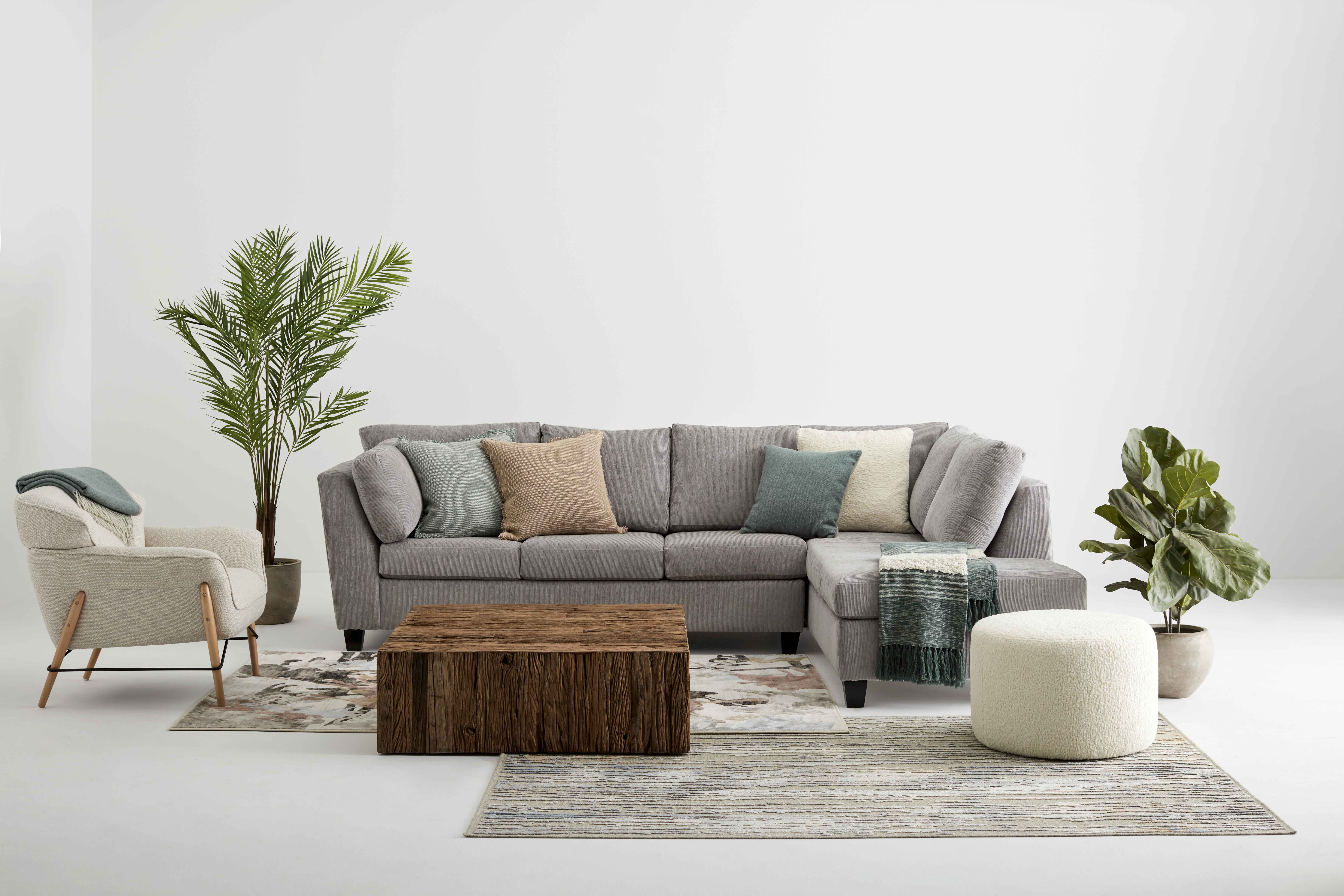 """View on a living room composed of a fabric sofa, a cosy accent chair and a """"sheep's wool"""" ottoman. Cushions and throws are accumulated on the sofa. On the floor, two carpets are layered"""
