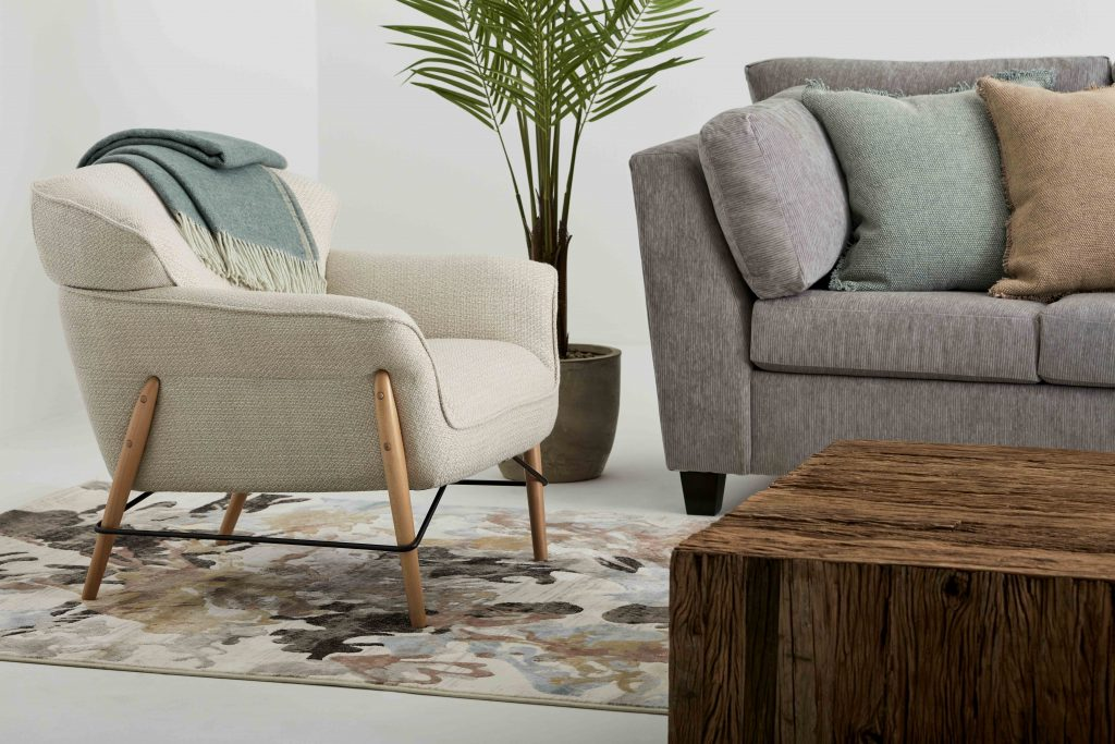 Fabrics: living room with a fabric armchair on which a blue throw is placed, accumulation of cushions on a grey fabric sofa, a wooden coffee table and a patterned carpet on the floor.