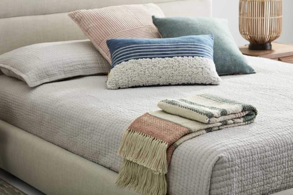 Fabrics: several textured cushions on a bed with a throw.