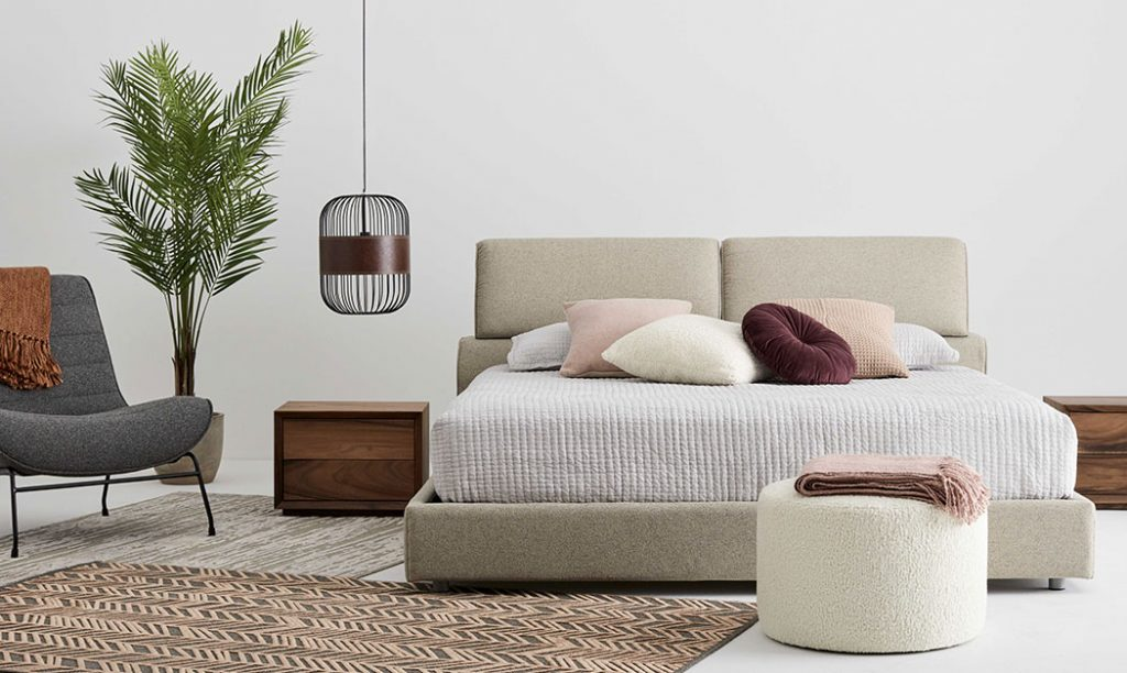 View on a bedroom with soft colours, composed of a beige fabric bed, a grey accent chair, a white ottoman and burgundy, white and pink cushions.