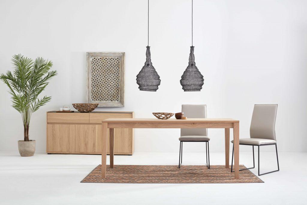 Collection NICOLAS - Vue sur une salle à manger épurée et minimaliste composée d'une table à manger en bois clair, deux chaises beiges, d'un buffet en bois et d'accessoires décoratifs.