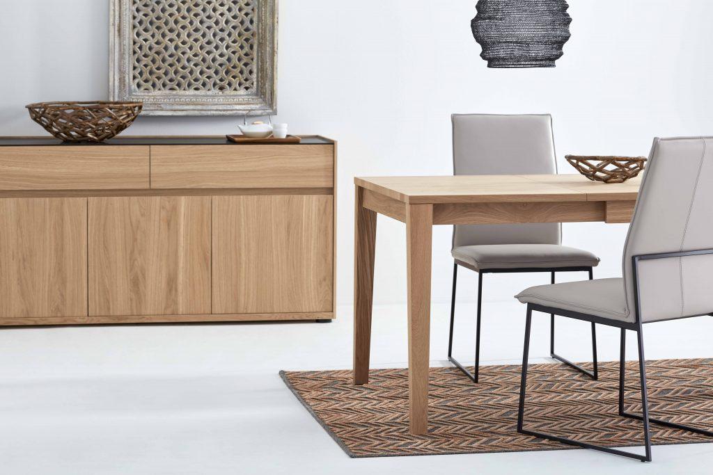 Collection NICOLAS - Plan resserré sur la table à manger et le buffet, tous les deux en bois clair.