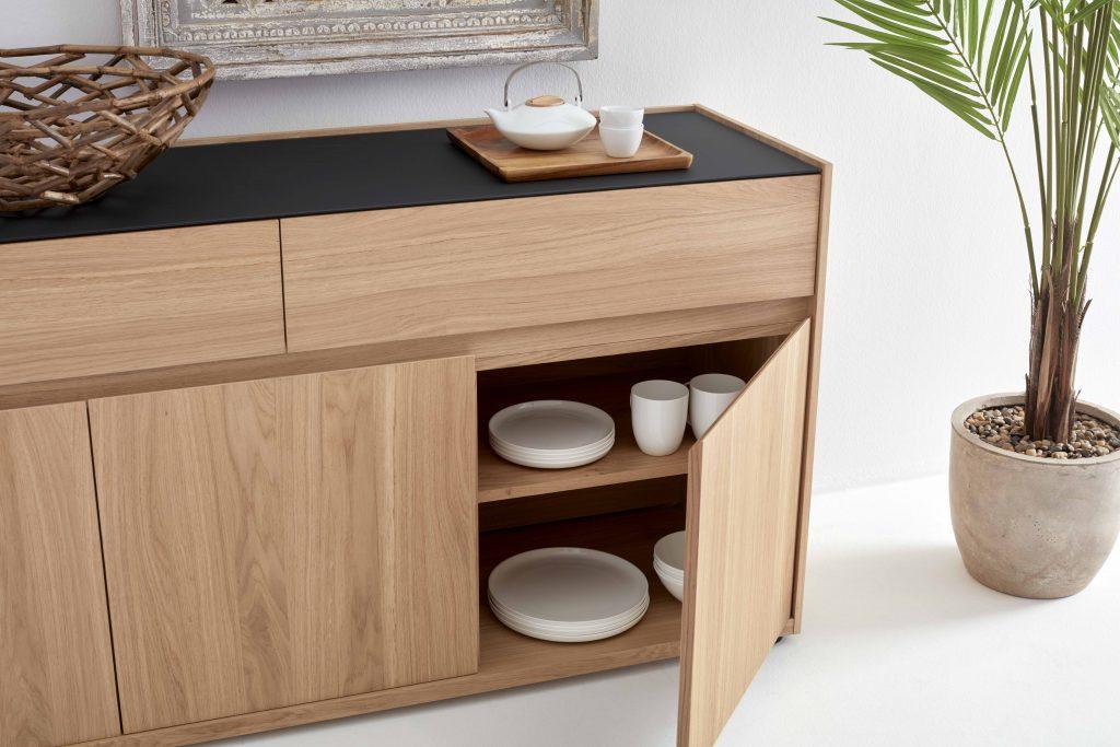 Collection NICOLAS - Vue sur le buffet en bois beige et plateau noir matifié laissant apercevoir de la vaisselle à l'intérieur.