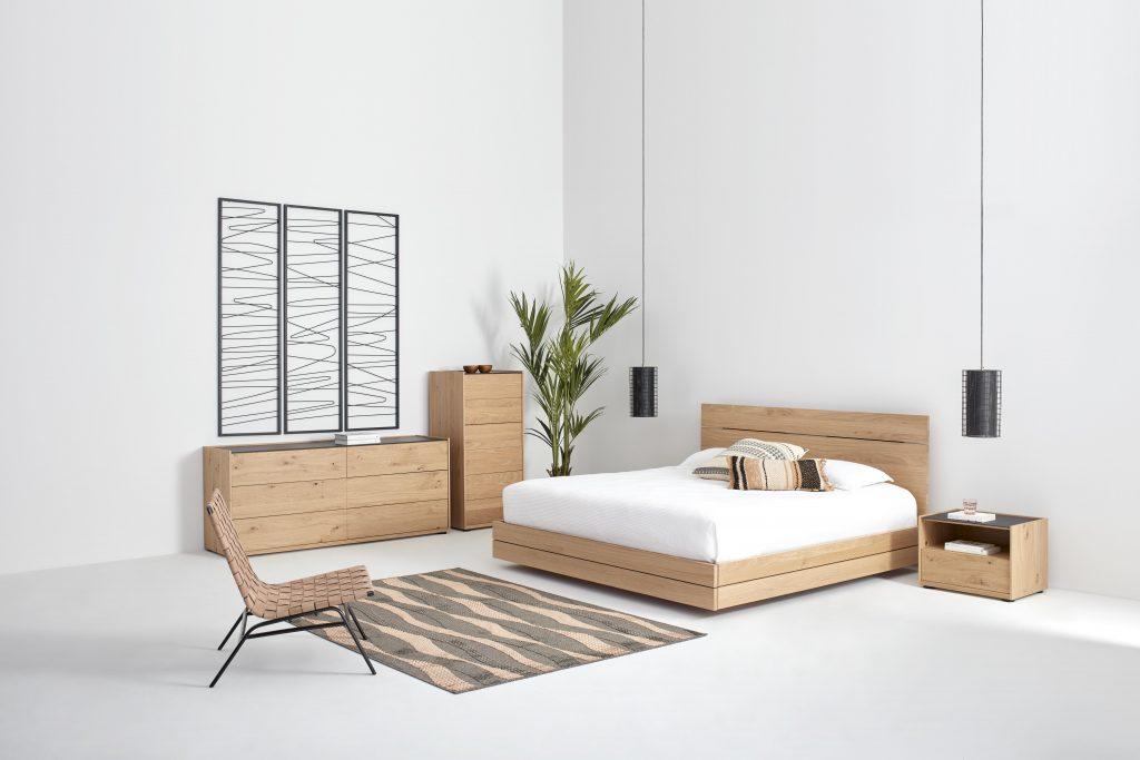 Collection NICOLAS - Vue sur une chambre à coucher épurée composée d'un lit en bois clair, d'une table de chevet, d'un chiffonnier et d'une commode. En retrait un fauteuil d'appoint, au sol un tapis et une plante et des luminaires au plafond.