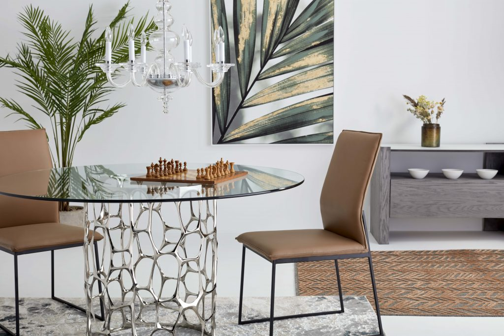 On a round glass table, a chess game is about to begin. Two beige leather chairs are placed around the table waiting for the players. In the background, an opened sideboard shows some dishes and a wall art is hung on the wall. Two carpets are superimposed on the floor.