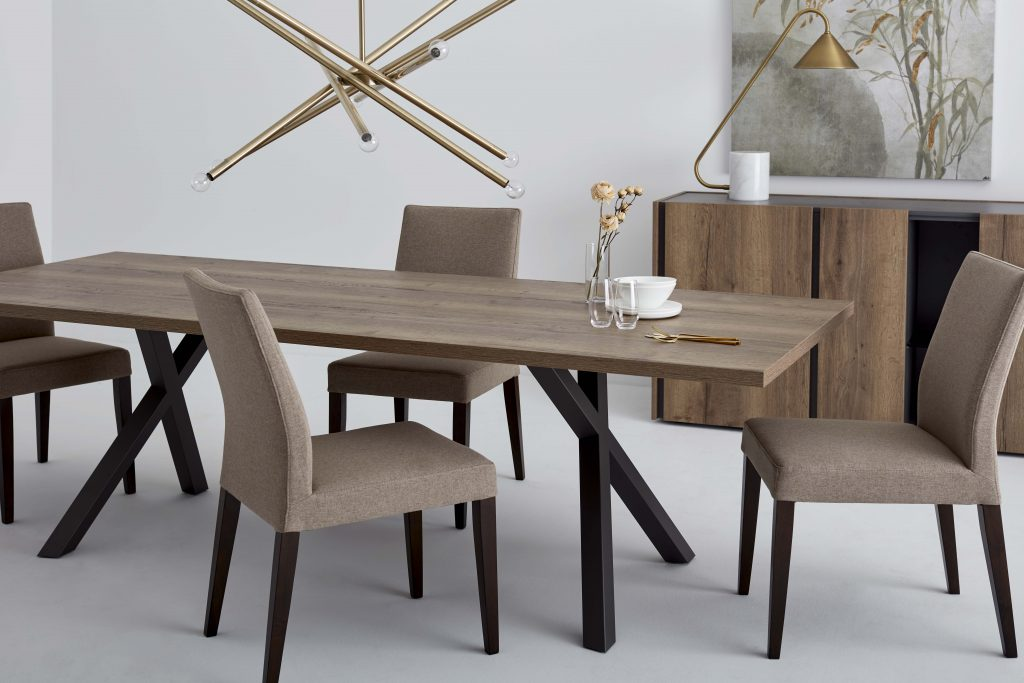 Four fabric chairs around a wooden table with X-shaped design legs. A pendant lamp overhangs the dining table on which dishes and some flowers in a vase appear. In the background, a table lamp and a wall art are placed on an open wooden sideboard.