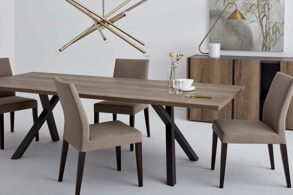 Quatre chaises en tissu autour d'une table en bois aux pieds design en forme de X. Une lampe suspendue surplombe la table sur laquelle apparait de la vaisselle et quelques fleurs dans un vase. En fond, une lampe et une toile sont logées sur un buffet en bois, ouvert.