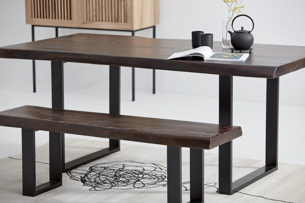 Une belle table en bois brun rectangulaire et son banc assorti sont disposés sur un tapis à motif. Sur la table, un magazine et un service à thé.