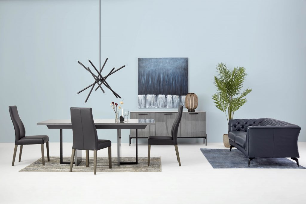 Dining room with a table and 3 chairs. A pendant lamp overhangs the table. Against the wall, a sideboard with a table lamp and a wall art. In the right corner, a leather sofa with Chesterfield inspiration invites you to relax. On the floor there are two area rugs under the table and under the sofa.