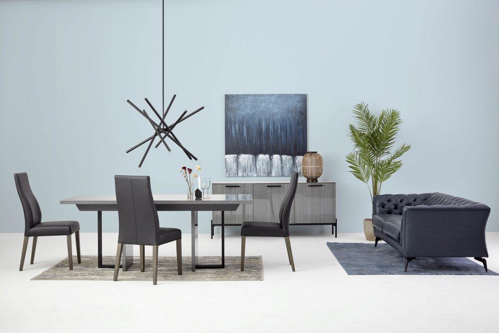 Salle à manger composée d'une table et 3 chaises. Au plafond, une lampe suspendue surplombe la table. Contre le mur, un buffet sur lequel est posé une lampe de table et un tableau. Dans le coin droit, un canapé en cuir aux inspirations Chesterfield invite à la détente. Au sol, deux tapis sont disposés sous la table et sous le canapé.