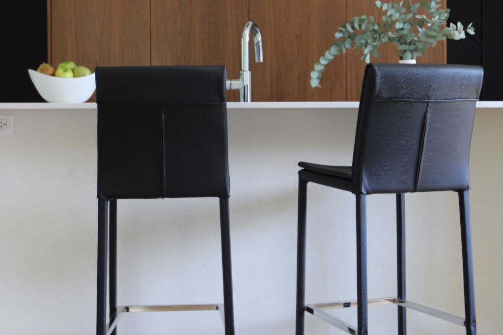 two black leather stools in front of a white counter