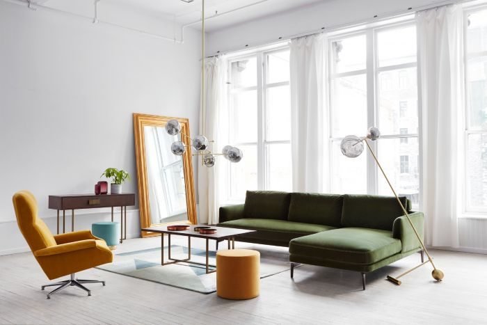Beautiful and bright living room with a green velvet sofa, a golden pendant lamp, an orange armchair and a golden foot lamp.