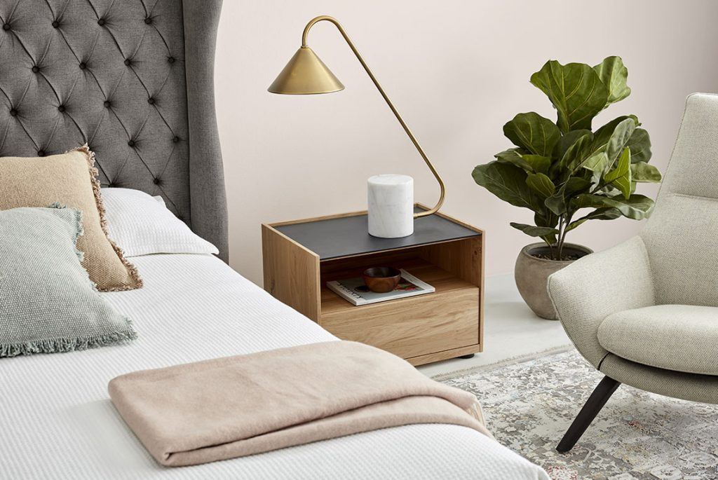 Close up on a cosy bedroom, with a throw and cushions laid on a grey fabric bed. On a wooden nighstand, a golden table lamp, next to which you can see a plant and a fabric armchair