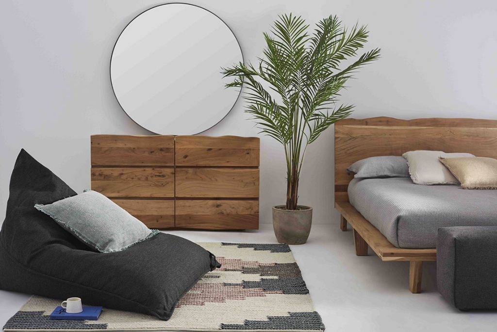 Light wooden bed and matching dresser, dark grey bean bag on the floor, with a blue cushion on it and a book+coffee on the side. A mirror is on the dresser and a plant is placed between the dresser and the bed.
