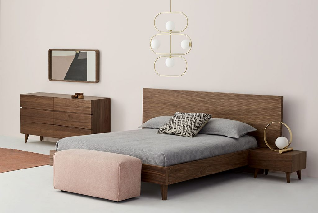 A dark wooden bed, dresser and nighstand, down the bed there's a pink fabric ottoman. Mirror on the wall and a golden pednant lamp just above the bed.